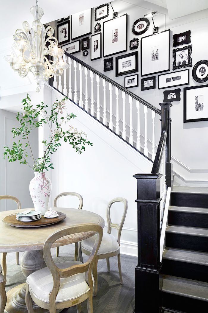Gallery wall of pictures up the staircase....Beautiful white walls with black trim