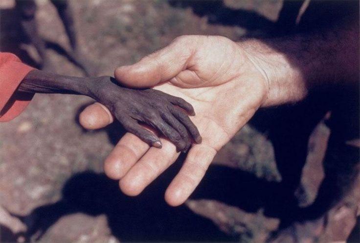 un missionnaire tenant la main d'un petit garçon.. le lieu de la photo se devine/ (Mike Wells)