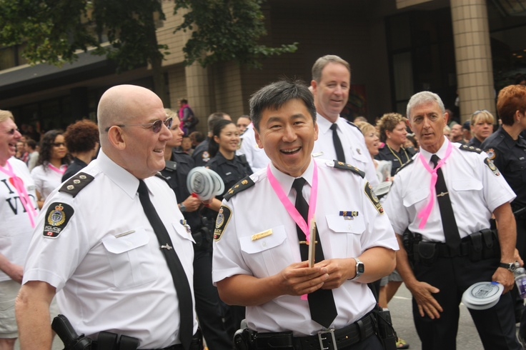 Chief Constable Jim Chu walking in the Pride Parade with his fellow officers.