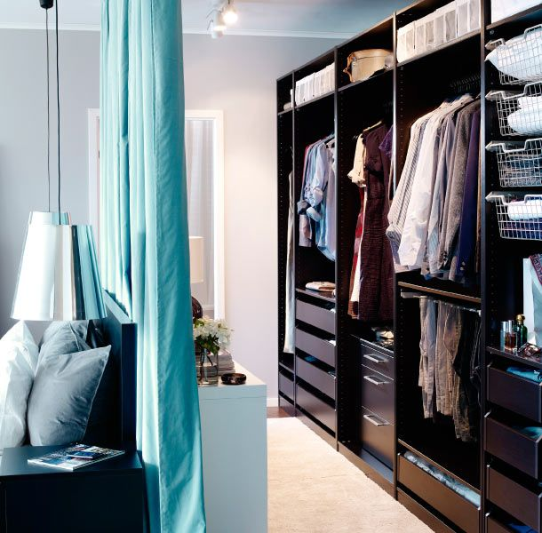 Create clever clothing storage. A little extra space behind your bed, a curtain behind the headboard, a PAX storage unit against the wall – and violá, a walk-through closet!