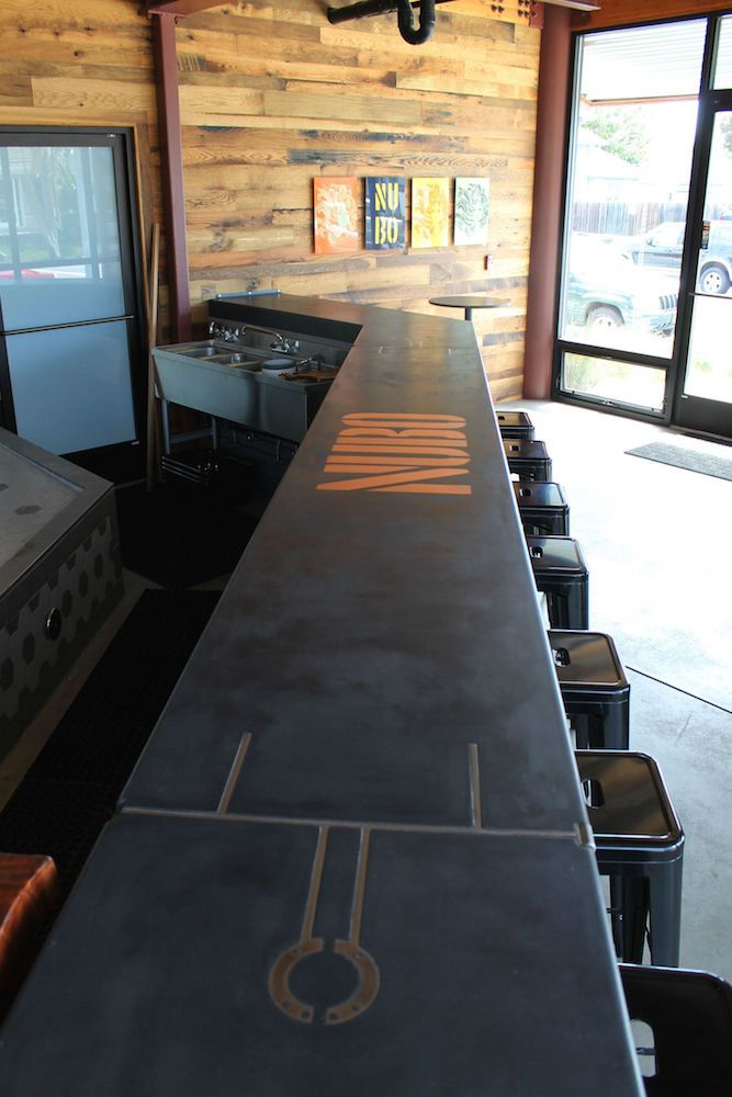 Industrial style concrete bar with steel and copper inlays.