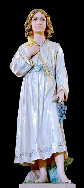 Statue of Jesus as a young teen. Jesus royalty is symbolized by the richness of his tunic and its high waistband. His prophetic life is symbolized by the forward position of his feet. And Jesus as priest and victim is symbolized by the eucharistic symbols of grapes and wheat.