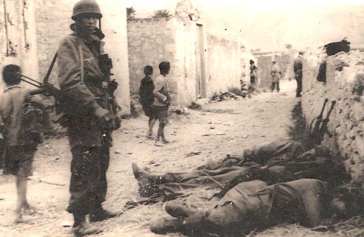Fallschirmjagers in Crete, 1941. Two are sleeping, one is standing guard, and in the background is two officers.