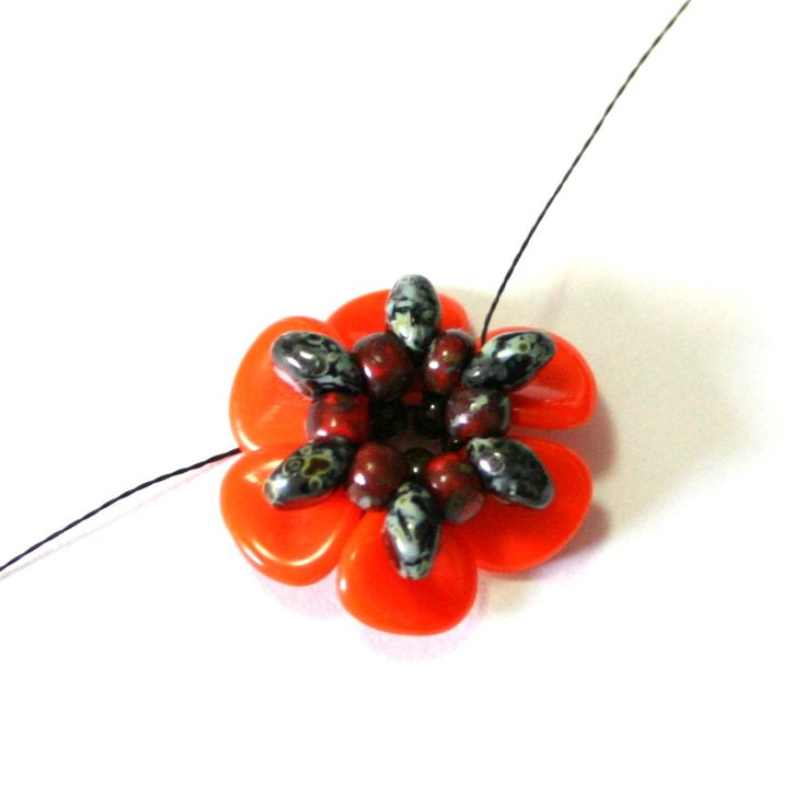Flanders Poppies made from beads, then turned into a bracelet. Designed by Aleksandra Lysenko. From Preciosa Ornela.