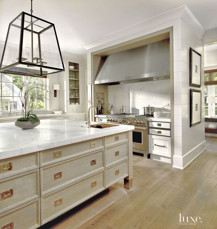 O'Brien Harris fabricated the kitchen's custom white cabinetry and cerused quarter-sawn white- oak island for homeowners and builders Bruce and Linda Ritter. The range is from Abt.