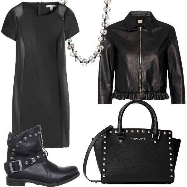 Un outfit rock, composto da tubino nero e giacca in pelle con chiusura a cerniera. Stivaletti bassi con fibbia alla caviglia e borsa borchiata con manico e tracolla. Completa il look la collana.