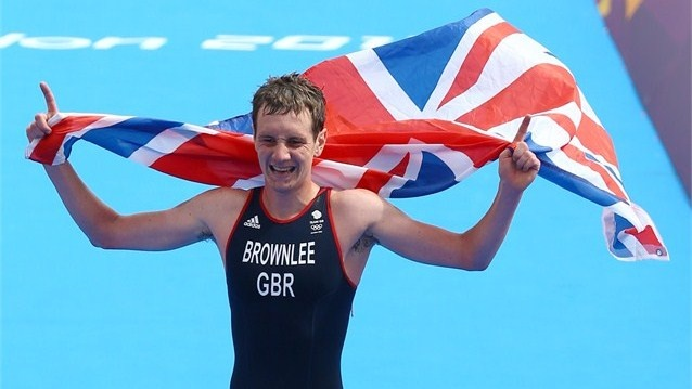 Alistair Brownlee of Great Britain holds a Union Jack aloft as he approaches the finish line to win gold during the Men's Triathlon on Day 11 of the London 2012 Olympic Games at Hyde Park.  (7aug2012)