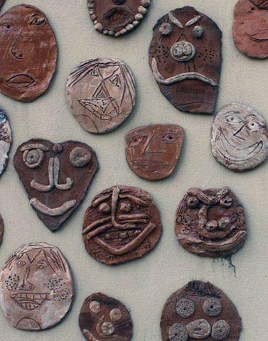Facce che crescono sul muro esterno della scuola arti e mestieri