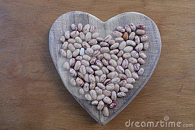 Creative composition for beans lovers with a wooden heart over a wooden board