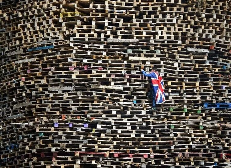 北爱尔兰 Northern Ireland 贝尔法斯特 Belfast,英国民众搭建巨型篝火堆为纪念博伊恩战役胜利日时点燃。摄影师: Charles McQuillan
