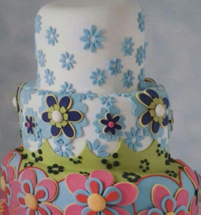 Torta a tre piani decorata con motivi floreali in pasta di zucchero