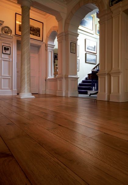 Historic house interior with expanse of oak boards and painted wall panelling