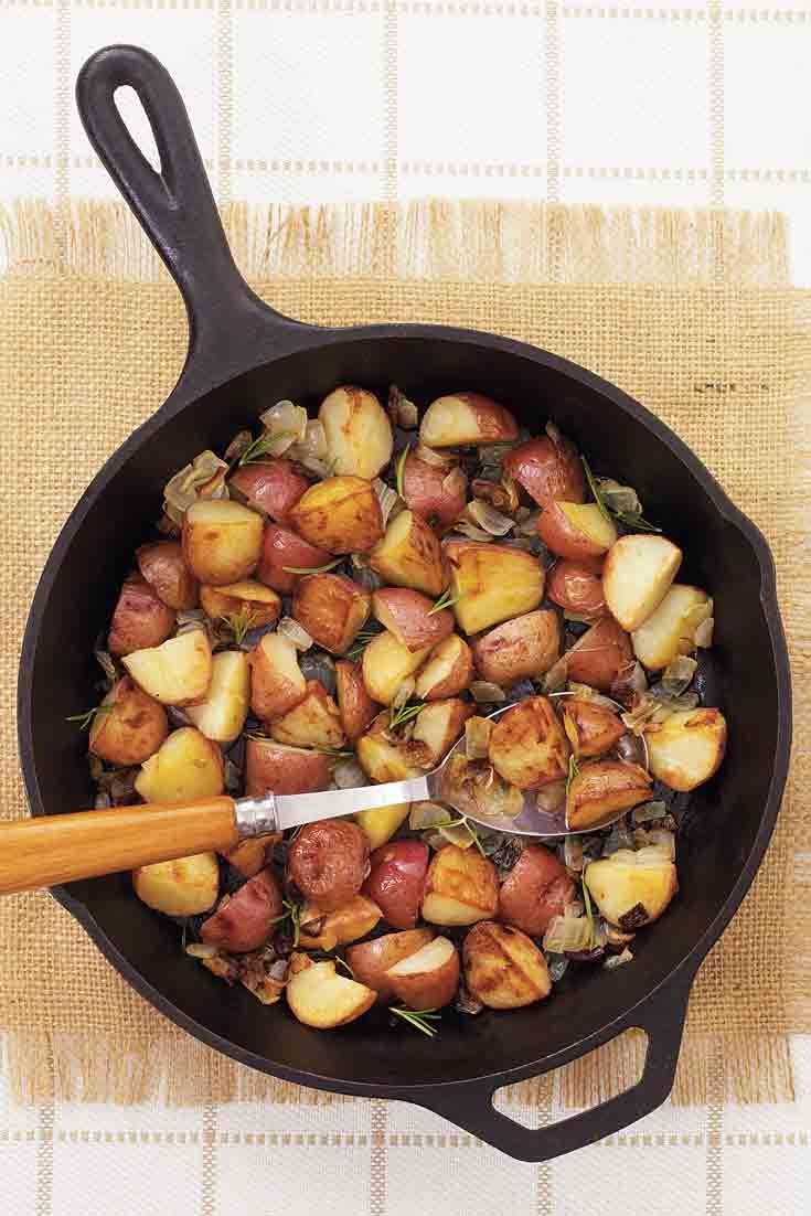 Roasted Red Potatoes with Rosemary and Onion cooked in a cast iron skillet.
