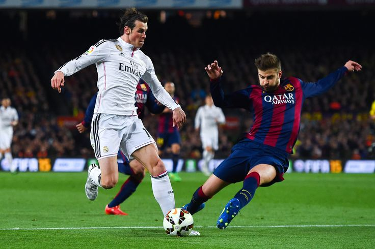 Gareth Bale of Real Madrid CF competes for the ball with Gerard Pique of FC Barcelona during the La Liga match Between FC Barcelona and Real Madrid CF at Camp Nou on March 22, 2015 in Barcelona, Catalonia.