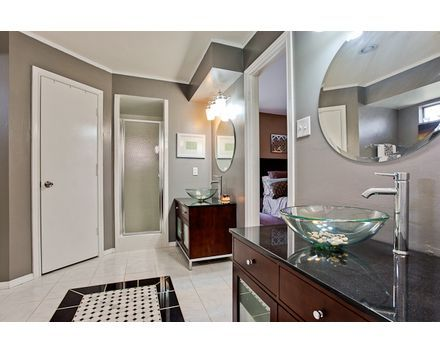 Granite vanity tops with vessel sinks. Granite and marble floor tiles. Light and bright!