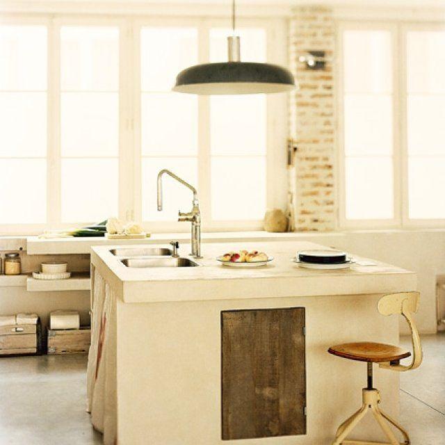 Une cuisine avec un îlot en béton blanc