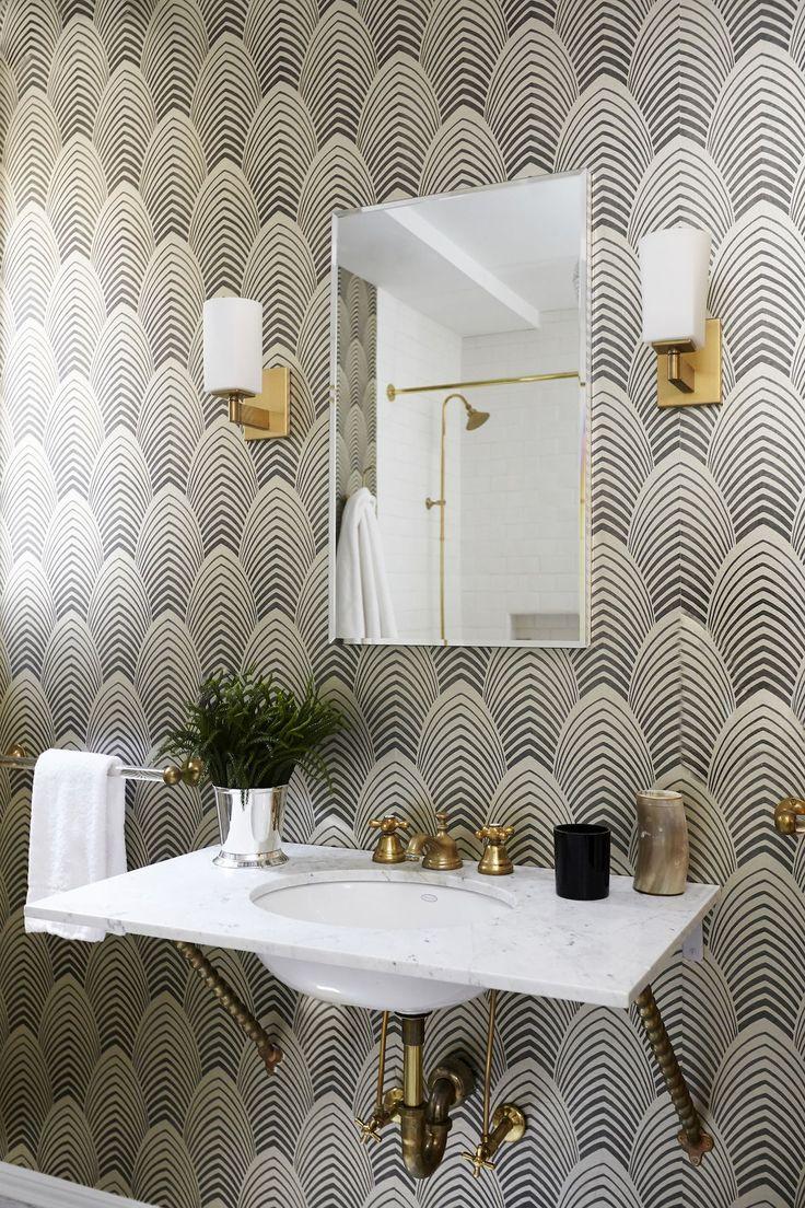 Sleek bathroom with brass fixtures & deco inspired wallpaper