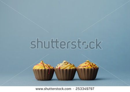 Three Chocolate Cup Cake over blue background