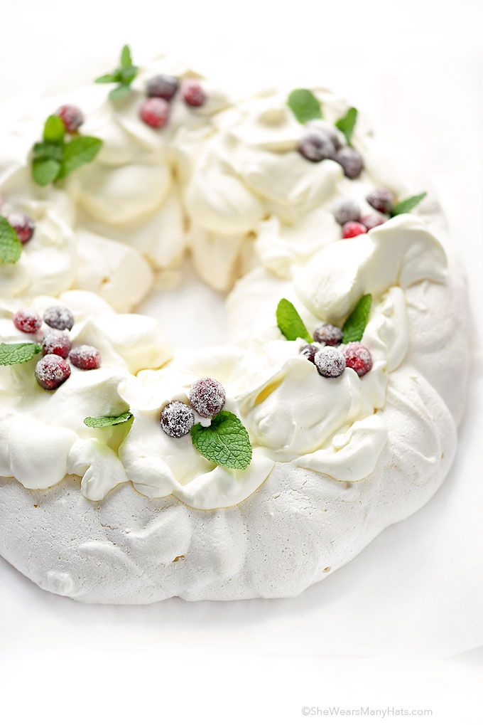 This festive Pavlova Wreath has a crispy crunchy shell and a marshmallowy interior topped with whipped cream, sugared cranberries and fresh mint.