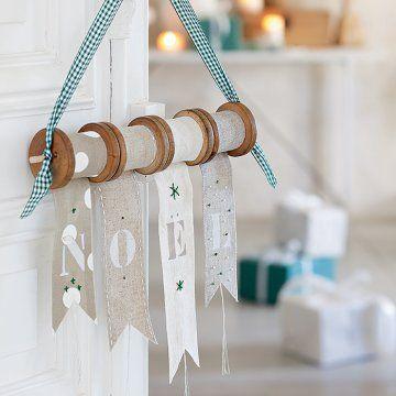 Un joli message Noël peint au pochoir sur des rubans installés sur des bobines de fil en bois!
