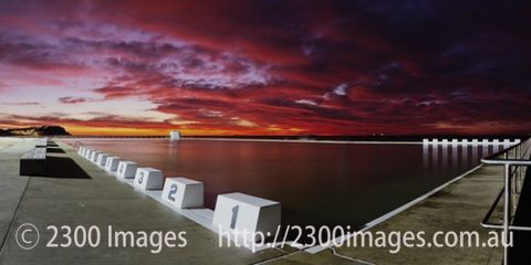 Red Skies Over Merewether Ocean Baths - A panorama with impressive clouds taken just before sunrise from the starting blocks at Merewether Ocean Baths,...