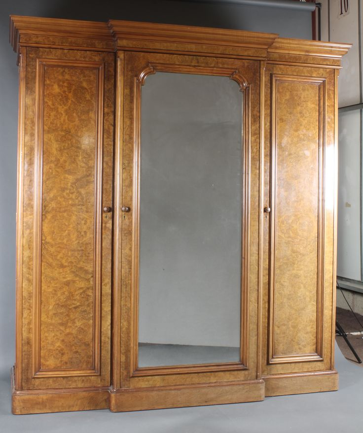 """Lot 984, A handsome Victorian figured walnut breakfront triple wardrobe with moulded cornice, the centre section fitted 5 trays above 3 long drawers with brass swan neck drop handles and enclosed by arched panelled mirrored door, flanked by a pair of wardrobes one with hanging shelf and drawer to base, the other fitted 6 brass and mahogany double sided coat hangers and a commode compartment, 87""""h x 80""""w x 24""""d, est  £300-500"""