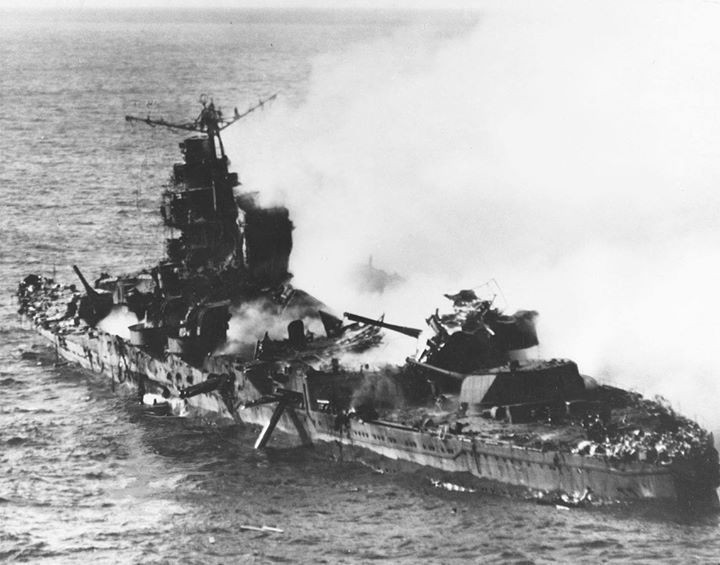 Japanese heavy cruiser Mikuma photographed from a USS Enterprise (CV-6) SBD aircraft during the Battle of Midway after she had been bombed by planes from Enterprise and USS Hornet (CV-8). Note her shattered midships structure torpedo dangling from the after port side tubes and wreckage atop her number four eight-inch gun turret.