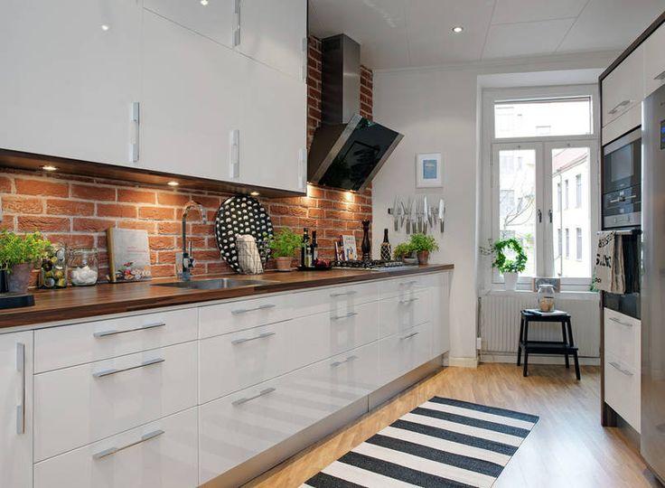 Długi rząd klasycznych dolnych i górnych szafek uzupełnia ustawiona przy przeciwległej ścianie wysoka zabudowa z piekarnikiem i lodówką. Biało-czarną kolorystykę ociepla nie tylko naturalna cegła, ale także drewniany blat i podłoga. / http://www.domzpomyslem.pl/wnetrza/galeria-wnetrz/kuchnia/styl-nowoczesny/cegla-nad-blatem,ta3:21,in958.html