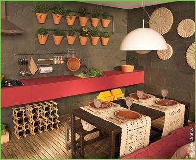 Esta varanda impõe personalidade, com bancada em Corian Vermelho, vasos pendentes com hortaliças, adega e mesa para refeições. A parede foi revestida com tijolo tipo lajota e o piso em deck de madeira.