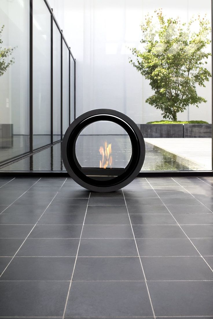 Extravagant fireplace steals the show stone fireplace for the spacious - Freestanding Bioethanol Fireplace With Panoramic Glass Roll Fire By Conmoto