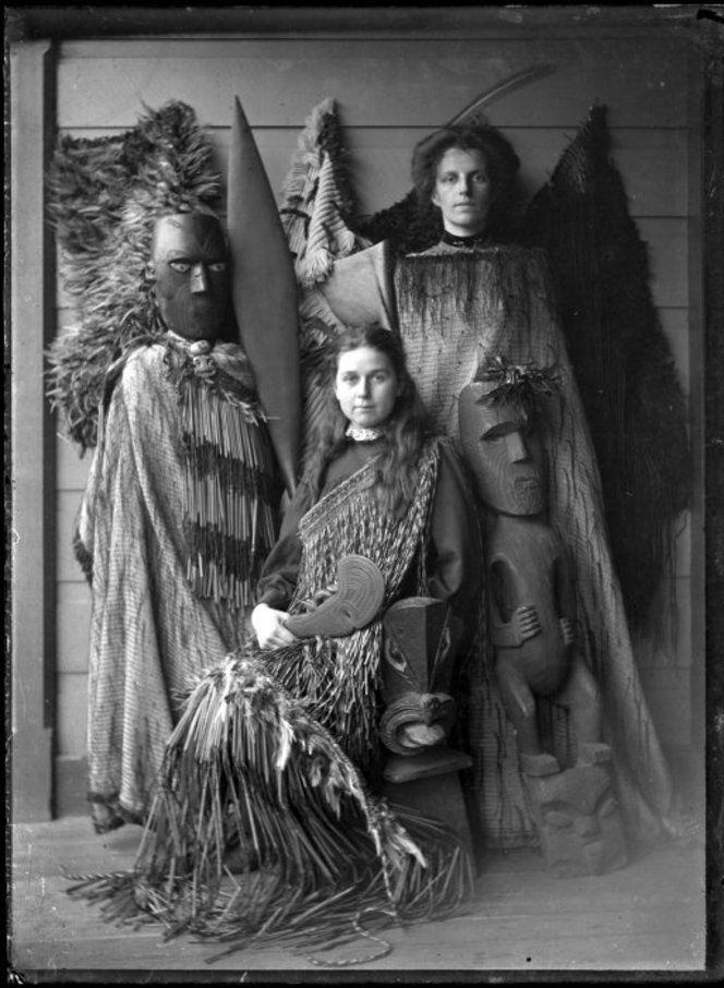 Two unidentified European women in a display of Maori cloaks, weapons, implements, and wooden carved figures.