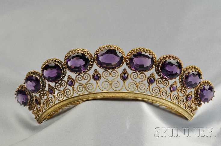 Antique Amethyst Tiara, set with nine cushion-cut amethysts graduating in size, framed by burr motifs, with circular-cut amethyst accents, within an elaborate scrolling 14kt gold mount.