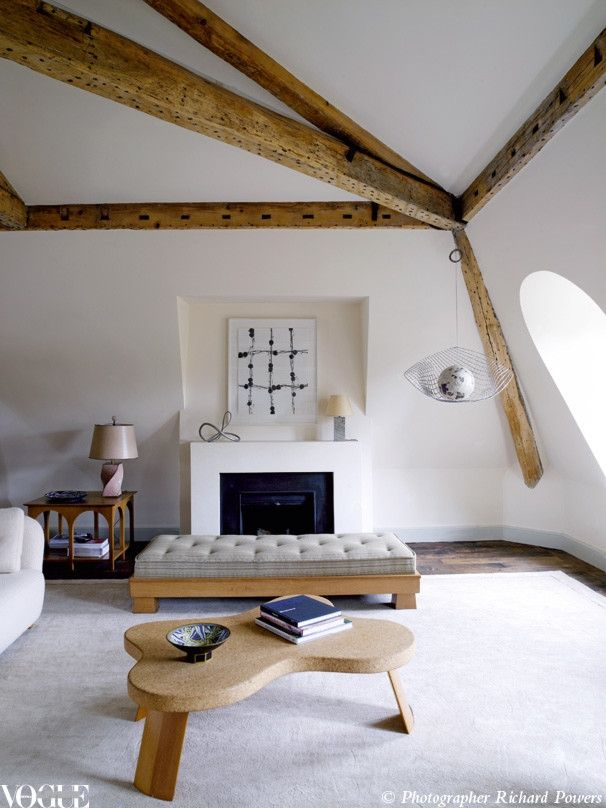Wooden beams and a cork board coffee table make bold statements in this serene attic. The neutral palette and low lying furniture maximises the limited space.