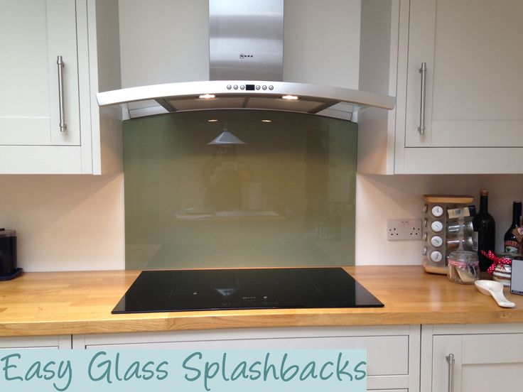 Svelte Green coloured glass splashback in a White Kitchen with Wooden Worktops. Visit easyglasssplashbacks.co.uk to discover more.