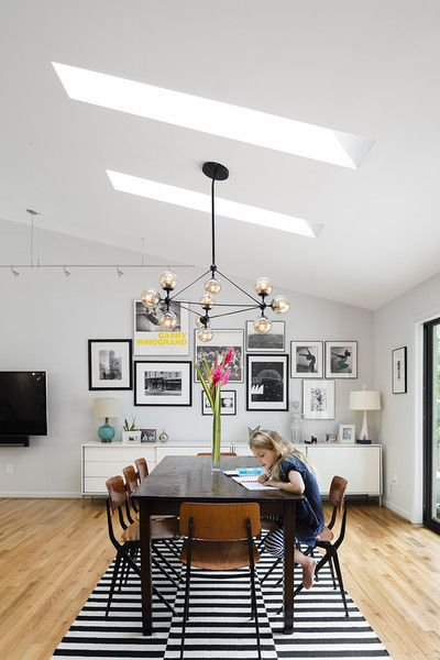 Modern home with dining room, ceiling lighting, table, light hardwood floor, chair, storage, and shelves. The dining area (above right) boasts circa-1955 Friso Kramer chairs. Photo 4 of The Bruning/Owen Residence