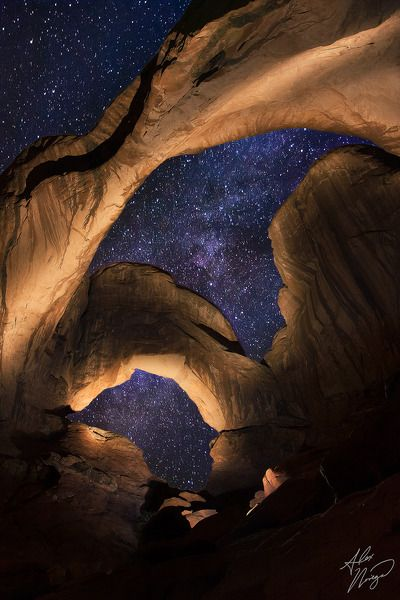 """Utah's Double Arch stands tall under the Milky Way on an autumn night. The arches were """"light painted"""" with my flashlight throughout the duration of the long exposure.  Equipment: Canon 40D, EF-S 17-55mm f/2.8    By Alex Noriega"""