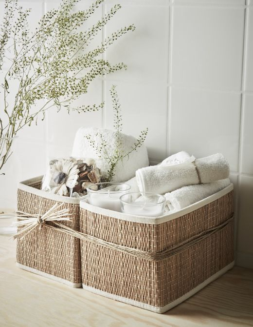 An at-home spa gift basket with washcloths, scented candles, potpourri and a towel