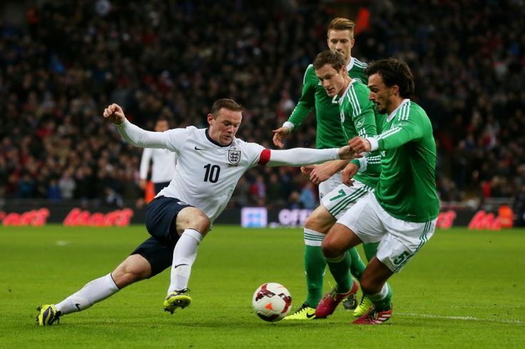 Wayne Rooney takes on Mats Hummels and Marcell Jansen