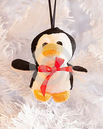 A close up of a cute little fluffy penguin decoration on a white Christmas tree branch.