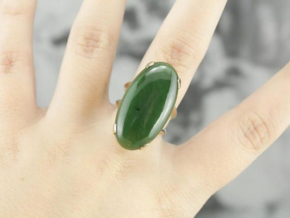 This substantial but simple design of this yellow gold mounting makes a great frame for this sleek, perfectly polished piece of Jade; that has a wonderful earthy green color and sophisticated look. Metal: 14K Yellow Gold Gem: Jade 20.93 Carats Gem Measurements: 16 x 30 mm, Oval Ring Size:
