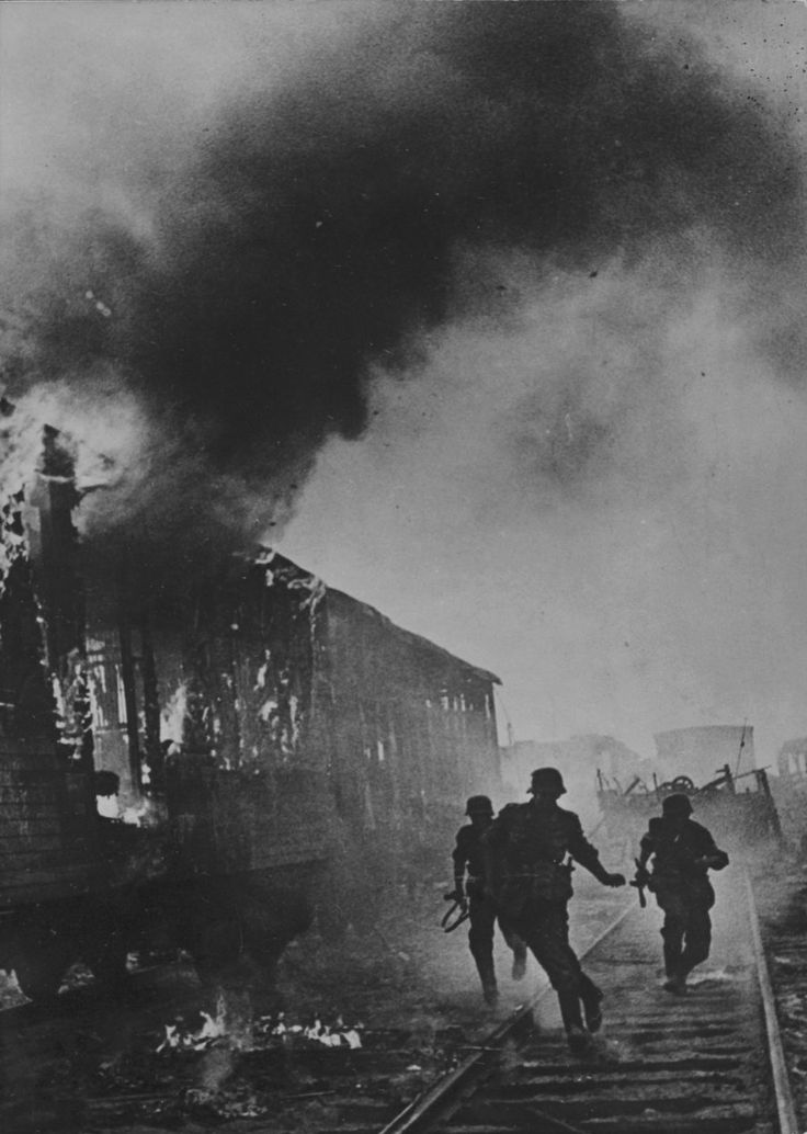 German troops on the offensive during the First Battle of Smolensk (July-Sept 1941) run past burning railroad cars. This battle turned out to be the first real strategic defeat for the Germans, who pushed through the Soviet cordon only with the most severe difficulty. Losses were substantial. Smolensk keenly contributed to the German defeat in front of Moscow in Dec 1941.