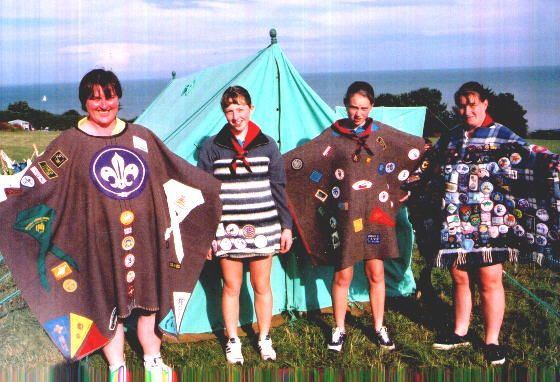 These are British Girl Guides who were camping at the former Kingsdown Scout Camp outside of Dover, England in the summer of 2000.  Notice that part of the tradition is to have a large central symbol that is sometimes hand stitched as you see with the leader on the left.  All of these are the poncho style with the center cut out.