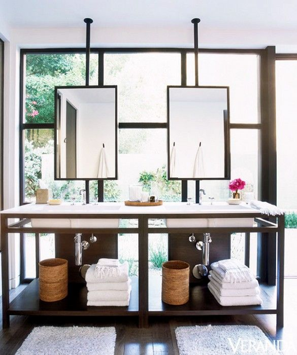 Bathroom vanity with mirrors hung in front of window.
