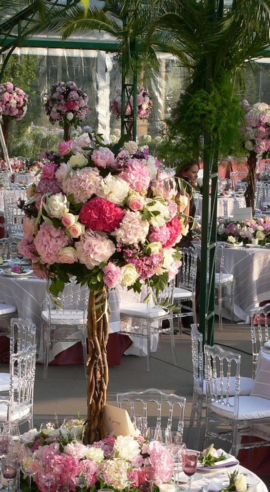 Wedding centerpieces are one of the greatest wedding ideas to happen to receptions. When your guests can admire all the floral beauty in the room AND enjoy a great conversation from across the table, well, that's when you know you have a good thing. If you're looking for a great way to incorporate tall centerpieces into your reception decor, think about using brilliant colors that pop, crystals that hang and reflect light, or cascading florals. We handpicked a few of our favorite tall…