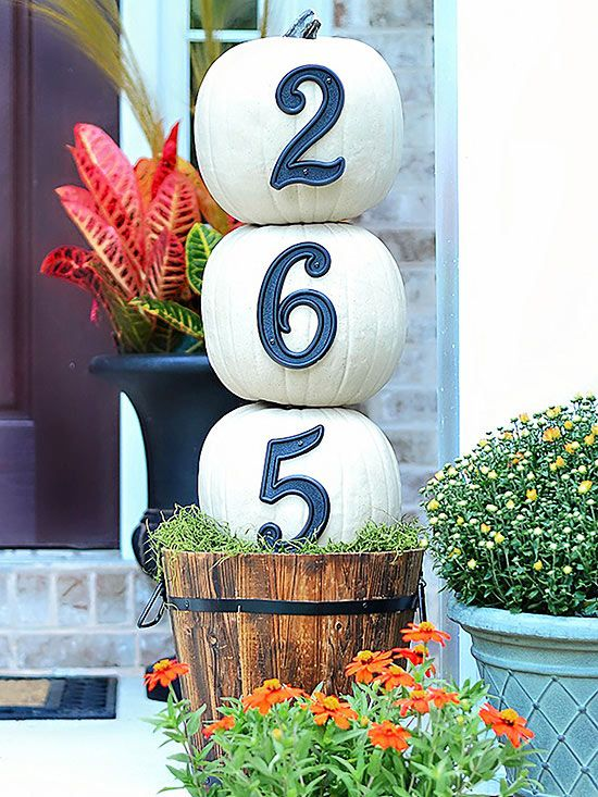 Announce your house numbers loud and proud with this festive, DIY topiary (and reuse it next year, since the pumpkins are artificial!). White pumpkins are outfitted with vintage-style house numbers, then threaded through a dowel for stability and stacked neatly over a wooden basket foundation. Vivid Spanish moss peeks over the basket top for added color.
