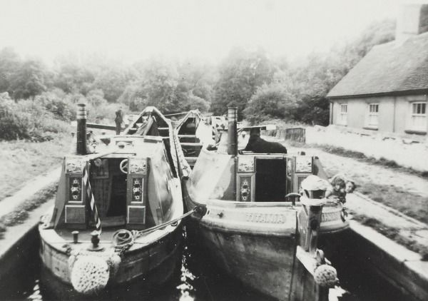 "BW192-3-2-2-13-1-293 Pair of British Waterways narrowboats in a lock at Watford on the Grand Union Canal Description Black and white photograph showing the pair 'Birmingham' and ""Titania"" breasted up in the lock. Shows the sterns of the boat with the open cabin doors which are painted with the same roses and castles decoration. There is a house beside the canal."