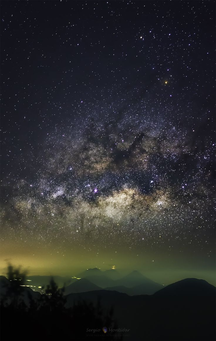 Milky Way over erupting volcano in Santa Maria, Guatemala, during the early morning hours of February 28, 2015. Visible on the ground are six volcanoes of the Central America Volcanic Arc, including Fuego, the Volcano of Fire, which is seen erupting in the distance. Visible in the sky, are many stars much further in the distance, as well as the central band of our Milky Way Galaxy situated horizontally overhead. (NASA-APOD)