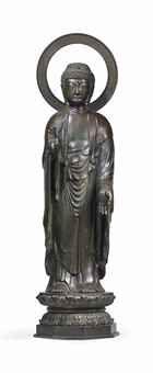 IMPORTANTE STATUE DE BOUDDHA AMITABHA EN BRONZE JAPON, EPOQUE MEIJI (1868-1912) Vêtu de robes monastiques souples, il est représenté debout sur une base lotiforme, ses deux mains en vitarkamudra et varadamudra. Son visage est serein devant un halo circulaire, ses yeux mi-clos sous des sourcils arqués. Son front est rehaussé de l'urna. Ses cheveux coiffés en petites boucles sont surmontés de l'ushnisha ; quelques défauts de fonte. Hauteur : 224 cm. (88 ¼ in.)