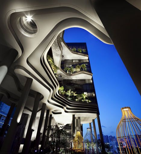 Balconies covered in tropical plants and contoured surfaces based on rock formations surround this Singapore hotel.