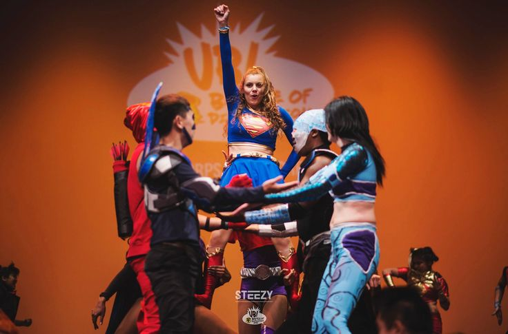 Supergirl gets a lift from her friends.  The Corps Dance Crew at Ultimate Brawl.  Photo by Steezy.  Super girl, blue beetle, aqua girl, cyborg, red arrow, cosplay, cosplayers, dance, dance crew, dancers, nerds, geek, geeks, dc comics, dc universe, san diego comic con, teen titans, young justice